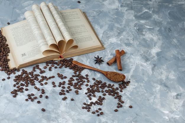 Kawa rozpuszczalna z książką, cynamon w drewnianej łyżce na jasnoniebieskim tle marmuru, zbliżenie.