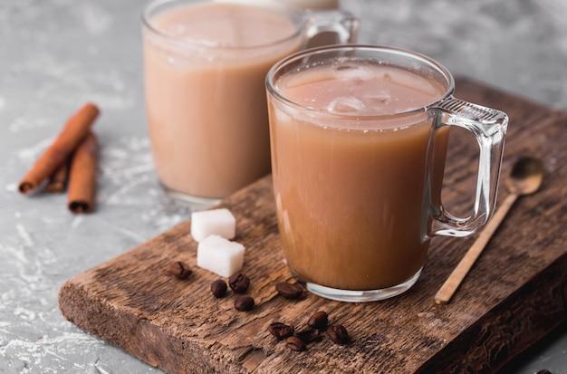 Kawa schłodzona z mlekiem, laski cynamonu, ziarna kawy, cukier, łyżka na stole.