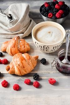 Kawa śniadaniowa z mlekiem i rogalikami, dżemem oraz świeżymi malinami i jeżynami