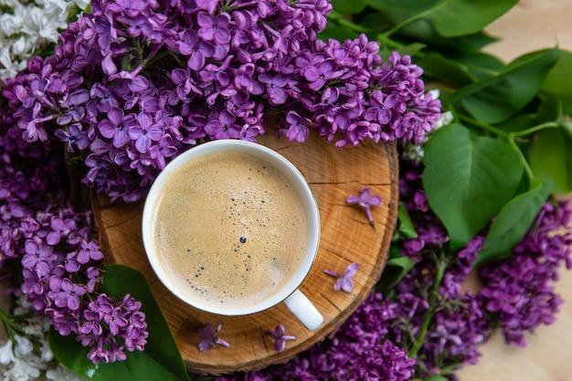 Kawa stoi na drewnianym konopie otoczonym kwiatami bzu