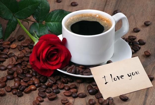 Kawa w białej filiżance. filiżanka kawy, palone ziarna kawy i czerwona róża na drewnianym stole
