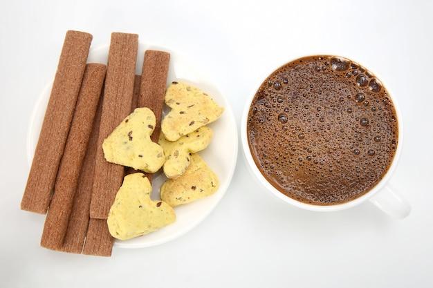 Kawa w białej filiżance na białym tle z ciasteczkami