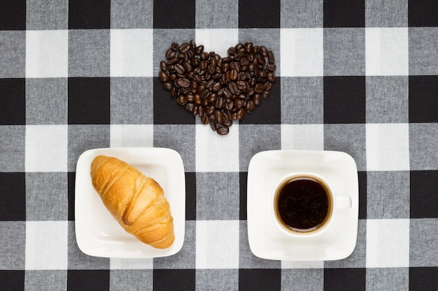 Kawa w białej filiżance, rogalik i serce z ziaren kawy