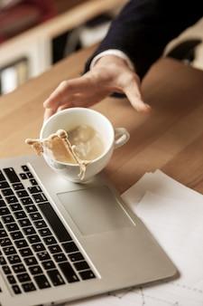 Kawa w białej filiżance rozlewa się na stole rano przy biurowym stołem