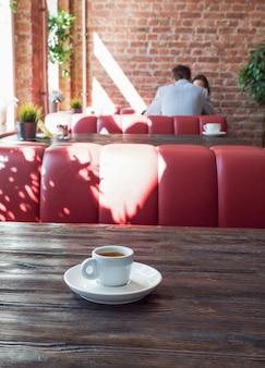 Kawa w białej filiżance stoi na drewnianym stole