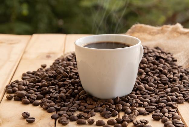 Kawa w białej filiżance z fasolą na drewnianym stole
