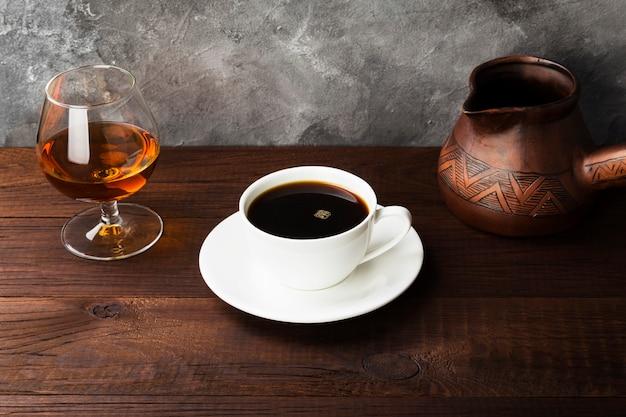 Kawa w białej filiżance z koniakiem i glinianym cezve na drewnianym stole