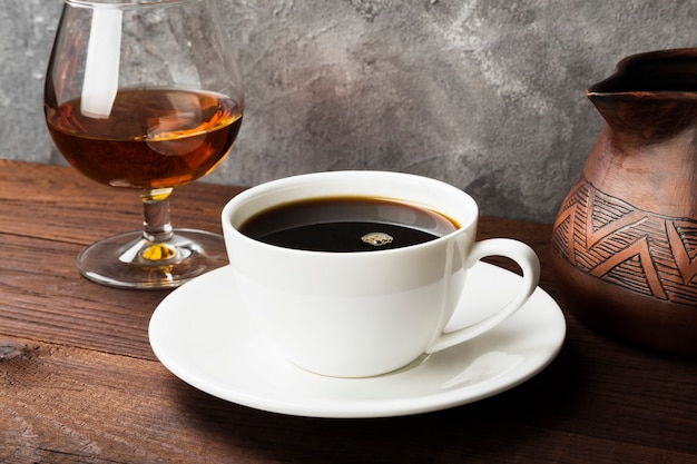 Kawa w białej filiżance z koniakiem i glinianym cezve