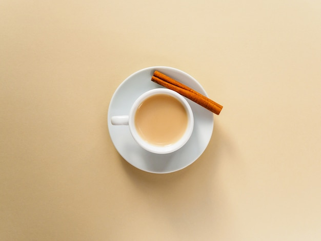 Kawa w białych filiżankach i laskach cynamonu na żółto.