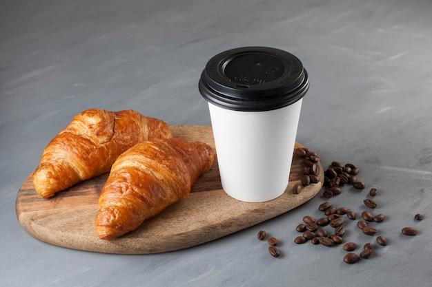 Kawa w białym papierowym kubku z pokrywką i parą świeżych rogalików na drewnianej desce do krojenia.