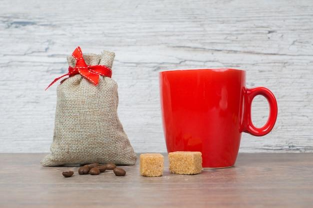Kawa w czerwonym kubku z torbą na prezent na drewnianym stole