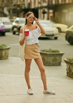 Kawa w drodze. młoda kobieta moda w modne letnie ubrania trzymając filiżankę kawy