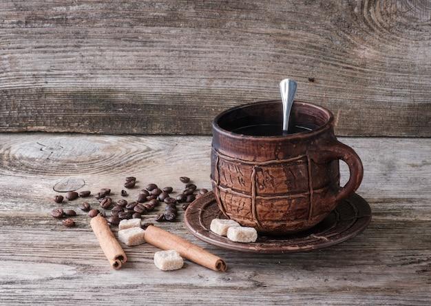 Kawa w dużym ceramicznym kubku na starej drewnianej desce.