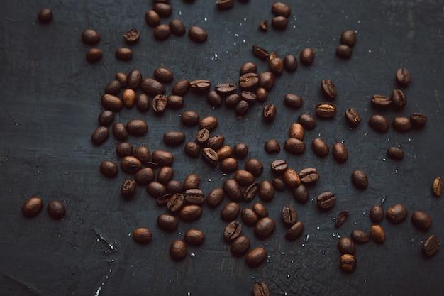 Kawa w fasolach na ciemnym tle, karmowy tło ziaren kawy