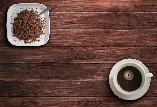 Kawa w filiżance i mielona kawa na drewnianym stole z widokiem