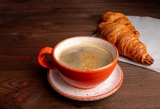 Kawa w filiżance i rogalik na ciemnym stole