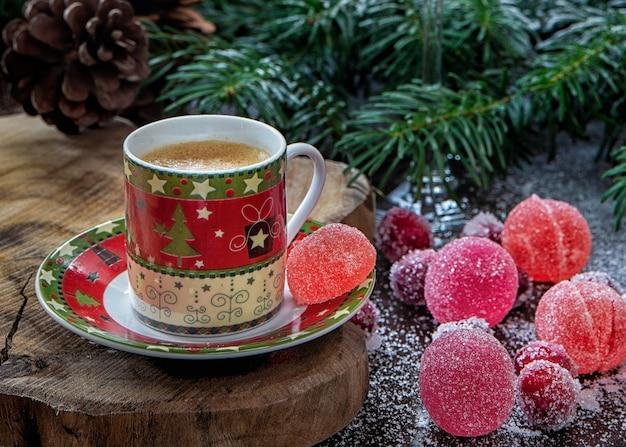 Kawa w filiżance świątecznej ze słodyczami, szyszką i gałązkami