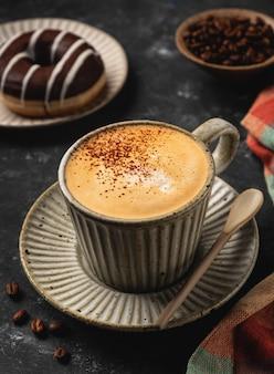 Kawa w filiżance z pączkiem i ziarnami kawy, ciemna