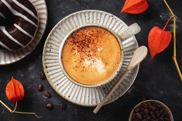 Kawa w filiżance z pączkiem, ziarnami kawy i kwiatami pęcherzycy