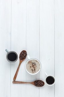 Kawa w filiżankach z ziaren kawy widok z góry na podłoże drewniane