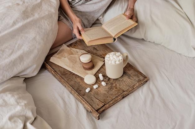 Kawa w łóżku. zgrabne kobiece nogi w ciepłych skarpetkach, drewniana taca na śniadanie do łóżka. dwie filiżanki kawy i pianki. koncepcja przytulnego domu. widok z góry