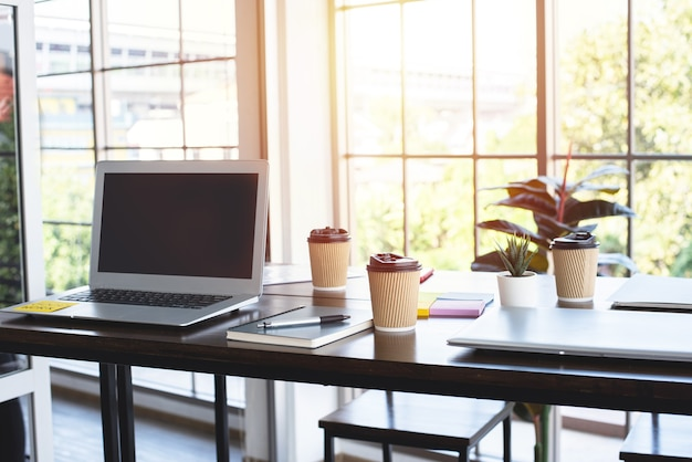 Kawa w papierowy kubek, laptop i notebook na drewnianym stole w biurze