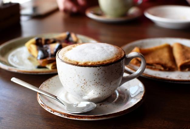 Kawa w pięknej ceramicznej filiżance na drewnianym stole w kawiarni na tle talerzy z naleśnikami. kawa cappuccino.