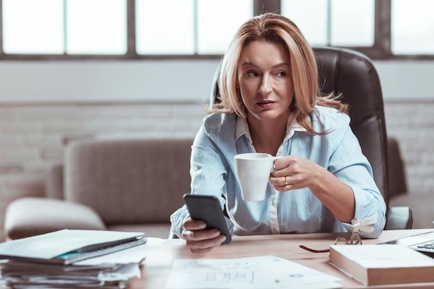 Kawa w pracy. piękny stylowy prawnik czuje ulgę i relaks przy kawie w pracy