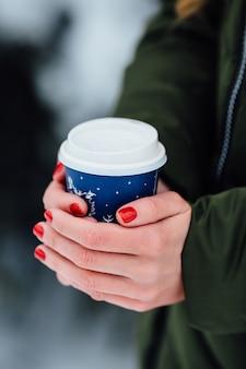Kawa w rękach. Kobiet ręki trzymają gorącą kawę w rękach outdoors w zima zimnym dniu