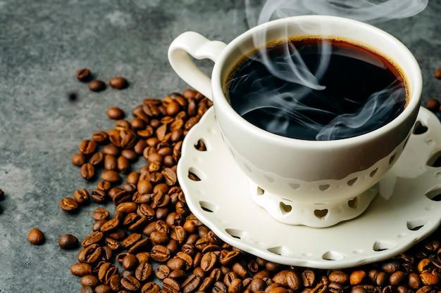 Kawa w tle. kawowe fasole i filiżanka na ciemnym tle. baner na kawę dla menu, projektowania i dekoracji