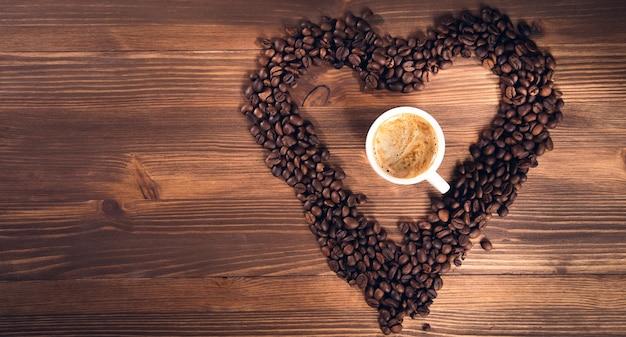 Kawa w ziarnach kawy jako serce na podłoże drewniane