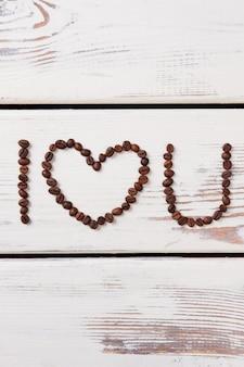 Kawa walentynkowa. kocham cię. serce z ziaren kawy na powierzchni drewnianych.
