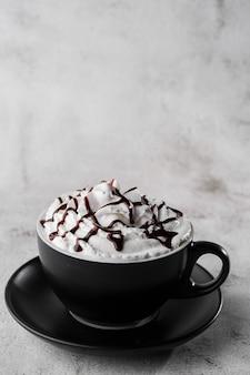 Kawa z bitą śmietaną i polewą czekoladową. mrożona kawa w ciemnej filiżance odizolowywającej na jaskrawym marmurowym tle. widok z góry, kopia przestrzeń. reklama menu kawiarni. menu kawiarni zdjęcie pionowe.