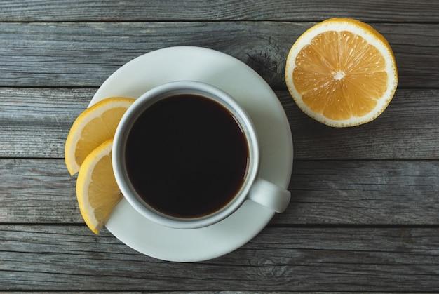 Kawa z cytryną na szarym drewnianym tle, widok z góry na stół