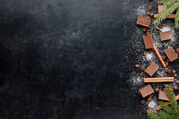 Kawa z czekoladowym shugar i cynamonem w bożych narodzeniach projektuje czarnego tła widoku kopii płaską przestrzeń