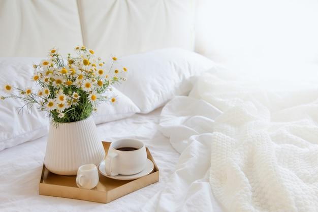 Kawa z kwiatami na tacy w łóżku