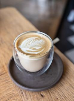 Kawa z latte art w filiżance na drewnianym stole w kawiarni lub kawiarni.