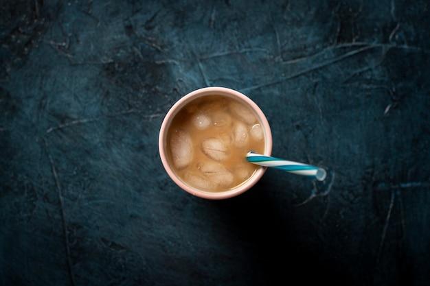 Kawa z lodem i mlekiem w szklance na ciemnym niebieskim tle kamienia. koncepcja napój chłodzący, pragnienie, lato, lód, życie nocne, klub. leżał płasko, widok z góry