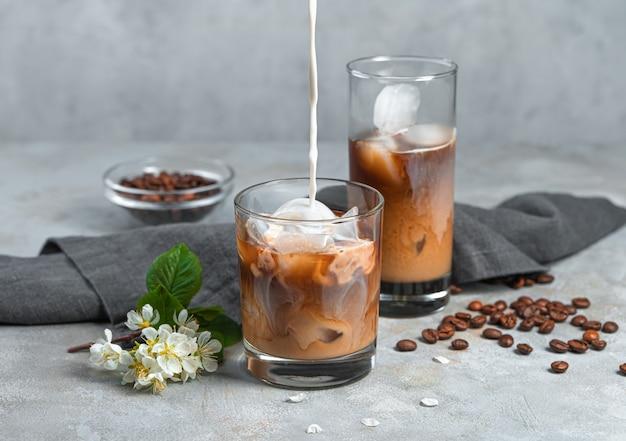 Kawa z mlekiem i lodem na szarej ścianie. wlewanie mleka do szklanki mrożonej kawy.