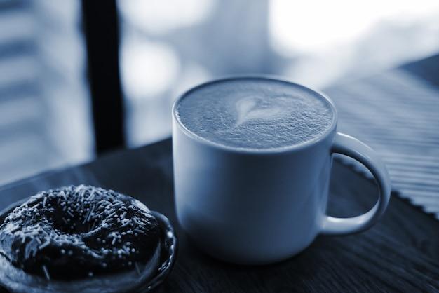 Kawa z narysowanym sercem i mlekiem na drewnianym stole w kawie. kolor koncepcji roku 2020. ścieśniać. pączek z rozsypaniem na stole obok kawy