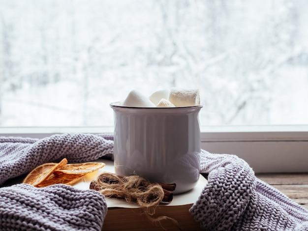 Kawa z piankami, cynamonem, książką i przytulnym szarym swetrem na zabytkowym parapecie na tle śnieżnego krajobrazu z zewnątrz. nieostrość. relaksujący zimowy dzień w domu z tradycyjnym zimowym gorącym napojem.