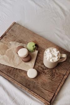 Kawa z piankami i makaronikami na drewnianej tacy, w łóżku. estetycznie piękna rama