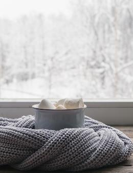 Kawa z piankami i przytulny szary sweter na parapecie vintage na tle śnieżnego krajobrazu z zewnątrz. nieostrość. relaksujący zimowy dzień w domu z tradycyjnym zimowym gorącym napojem. minimalistyczny styl.