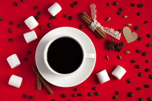 Kawa z przyprawami i ptasie mleczko na czerwonym tle włókienniczych. walentynki
