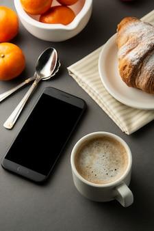 Kawa z rogalikami i owocami cytrusowymi. stół roboczy z inteligentnym telefonem. ciasto francuskie i filiżanka kawy.