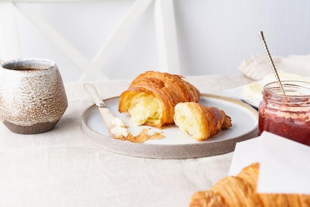 Kawa z rogalikiem. jasny, słoneczny poranek, spokojne śniadanie ze świeżymi wypiekami, widok z boku