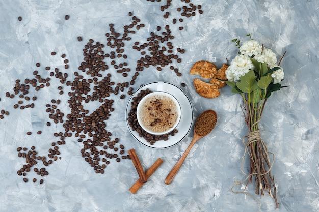 Kawa z widokiem z góry z mieloną kawą, ziarnami kawy, kwiatami, laskami cynamonu, ciasteczkami na nieczysty szarym tle. poziomy