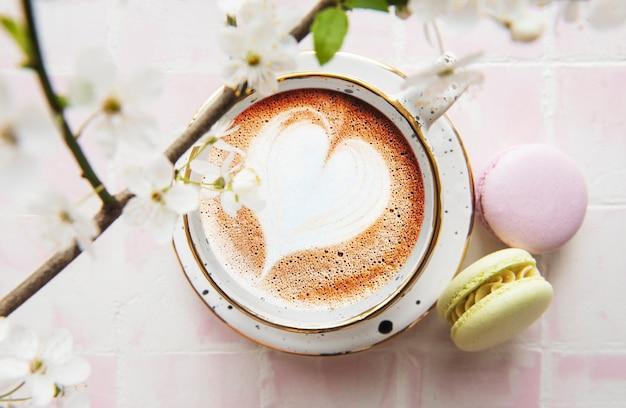 Kawa z wzorem w kształcie serca i słodkimi makaronikami na różowym tle kafelkowym