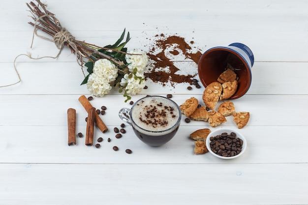 Kawa z ziaren kawy, ciasteczka, kwiaty, laski cynamonu w filiżance na podłoże drewniane, wysoki kąt widzenia.