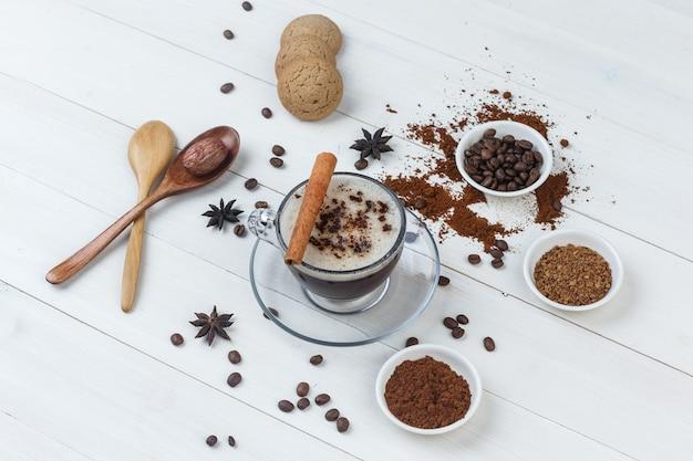 Kawa z ziaren kawy, kawa mielona, przyprawy, ciasteczka, łyżki drewniane w filiżance na podłoże drewniane, duży kąt widzenia.